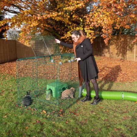 Una donna fuori all'aperto in autunno con due conigli nel recinto